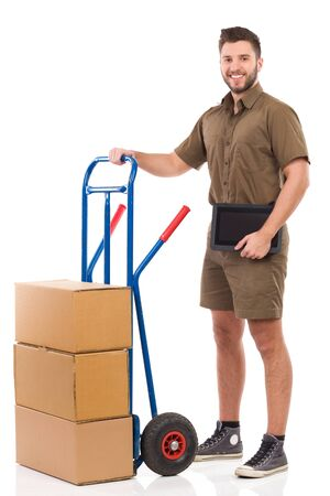 leaning on the truck: Cheerful delivery man standing with a push cart and holding digital tablet. Full length studio shot isolated on white. Stock Photo