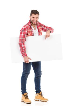 lumberjack shirt: Man in lumberjack shirt holding blank placard and pointing