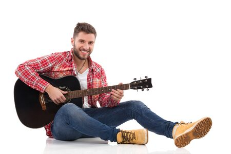 lumberjack shirt: Guitarist in red lumberjack shirt sitting on a floor and play the black acoustic guitar. Full length studio shot isolated on white. Stock Photo