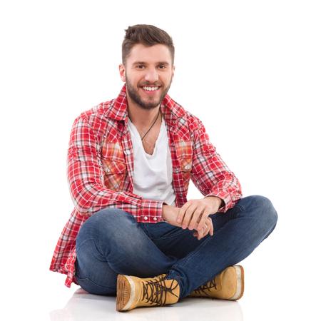 ジーンズと床に足を組んで座ってランバー ジャック シャツでハンサムな若い男。完全な長さのスタジオ撮影に分離白。