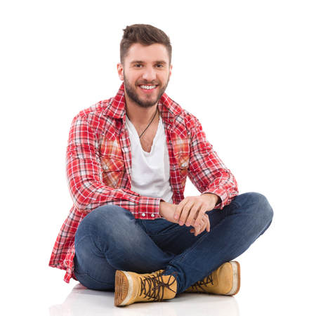 Handsome young man in jeans and lumberjack shirt sitting on floor with legs crossed. Full length studio shot isolated on white.
