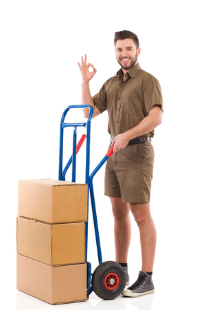 push cart: Cheerful delivery man standing with a push cart and showing ok sign. Full length studio shot isolated on white. Stock Photo