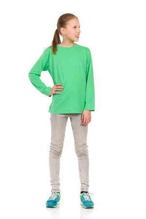 Smiling girl in green blouse, jeans and sneakers, posing with hand on hip and looking away. Full length studio shot isolated on white.
