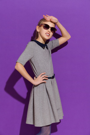 preadolescence: Young girl in sunglasses posing in gray dress. Three quarter length studio shot on violet background Stock Photo