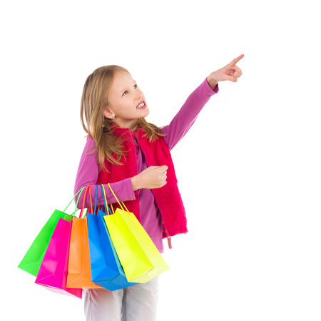 three quarter length: Young girl with colorful shopping bags pointing. Three quarter length studio shot isolated on white.