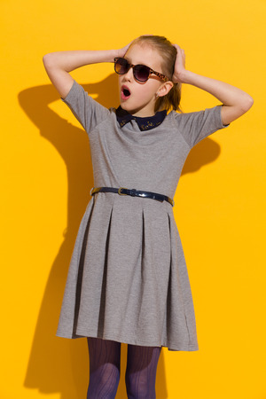 modern girls: Surprised girl in sunglasses and gray dress standing, holding head in hands and looking away. Three quarter length studio shot on yellow background.
