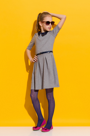 Young girl in sunglasses and gray dress posing with hand on hip. Full length studio shot on yellow background Stock Photo