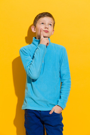 preadolescence: Thinking young boy standing and holding index finger on a chin. Three quarter length length studio shot on yellow background. Stock Photo