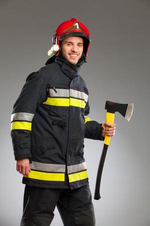three quarter: Smiling firefighter in red helmet holding an axe. Three quarter length studio shot on gray background.