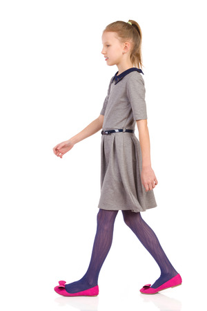 cool people: Little girl walking in gray dress, side view. Full length length studio shot isolated on white. Stock Photo