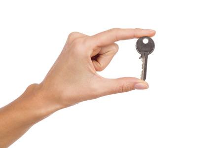 manos sosteniendo: Cerca de la mano de la mujer la celebraci�n de una clave en los dedos. Tiro del estudio aislado en blanco. Foto de archivo