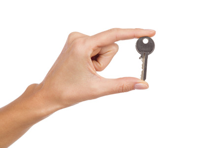 holding close: Close up of womans hand holding a key in fingers. Studio shot isolated on white.