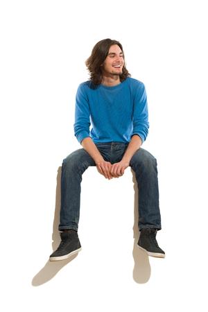 Jonge man zittend op een banner, lacht en kijkt weg. Full length studio shot geïsoleerd op wit.