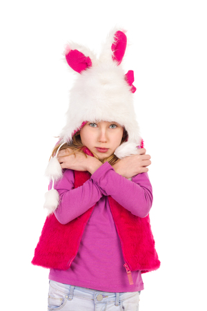 preadolescence: Girl in funny fur hat is standing and cuddle herself. Full length length studio shot isolated on white.