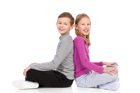 preadolescence: Happy boy and girl sitting on the floor with legs crossed and looking at camera. Full length studio shot isolated on white.