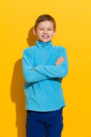 little boys: Young boy posing with arms crossed. Three quarter length studio shot on yellow background. Stock Photo