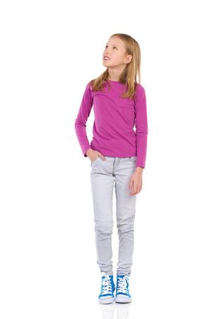 in jeans: Ni�a de pie con la mano en el bolsillo y mirando hacia arriba. Estudio de longitud completa aislado disparo en blanco.
