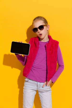 three quarter length: Young blond girl showing a digital tablet. Three quarter length studio shot on yellow background.