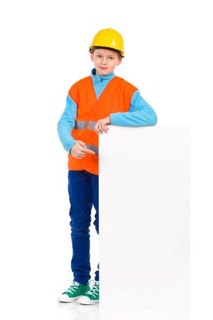reflective vest: Relaxed young boy in yellow hard hat and orange reflective vest standing close to white banner and pointing. Full length studio shot isolated on white.