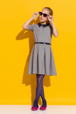 legs crossed on knee: Girl in sunglasses and gray dress posing in the sunlight. Full length studio shot on yellow background