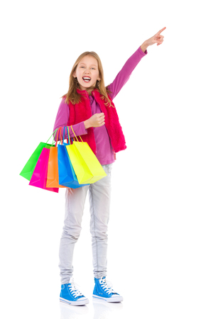 preadolescence: Young girl with colorful shopping bags pointing. Full length studio shot isolated on white.