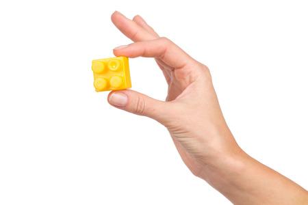 yellow block: Close up of womans hand holding yellow block. Studio shot isolated on white. Stock Photo