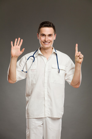 three quarter: Portrait of a smiling doctor showing number six with his fingers. Three quarter length studio shot on gray background.
