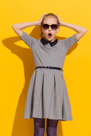 ni�as peque�as: Surprised girl in sunglasses and gray dress standing and holding head in hands. Three quarter length studio shot on yellow background.