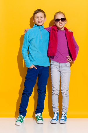 two girls hugging: Girl and boy posing and embrace each other. Full length length studio shot on yellow background. Stock Photo