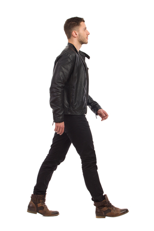 黒革のジャケットと黒のジーンズで歩く人。完全な長さのスタジオ撮影に分離白。