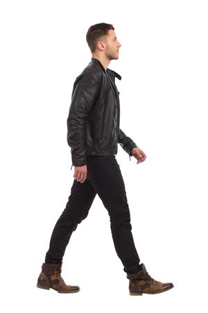 caminando: hombre que camina en la chaqueta de cuero negro y pantalones vaqueros negros. Estudio de longitud completa aislado disparo en blanco.