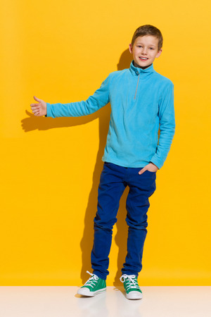 full shot: Young boy standing and showing thumb up. Full length length studio shot on yellow background. Stock Photo