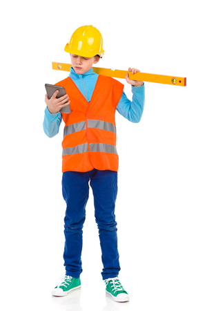 reflective vest: Young boy in yellow hard hat and orange reflective vest holding a spirit level on his shoulder and looking at digital tablet. Full length studio shot isolated on white. Stock Photo