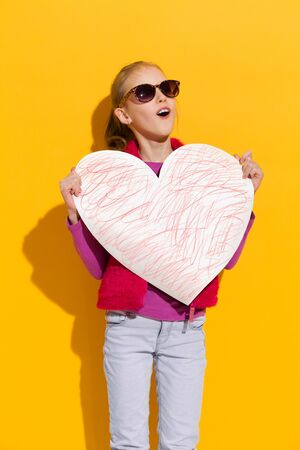 three quarter length: Young blond girl posing with big paper heart. Three quarter length studio shot on yellow background.