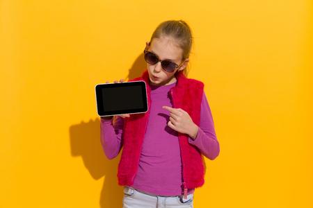 sunglasses: La muchacha rubia joven que se�ala en una tableta digital. La cintura para arriba foto de estudio sobre fondo amarillo. Foto de archivo