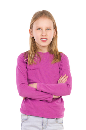 Little girl posing with arms crossed. Waist up studio shot isolated on white.