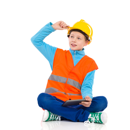 reflective vest: Young boy in yellow hard hat and orange reflective vest sitting on a floor with legs crossed, holding a digital tablet and looking away. Full length studio shot isolated on white. Stock Photo