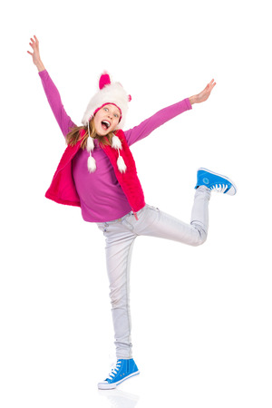 Girl in funny fur hat is standing on one leg and shouting with arms outstretched. Full length length studio shot isolated on white. Standard-Bild
