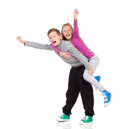 two girls hugging: Smiling boy carrying his sister on his back with their hands outstretched. Full length studio shot isolated on white.