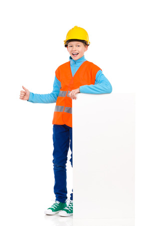 reflective vest: Young boy in yellow hard hat and orange reflective vest standing close to white banner and showing thumb up. Full length studio shot isolated on white.