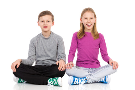 legs crossed on knee: Happy boy and girl sitting on the floor with legs crossed and holding hands on knees. Full length studio shot isolated on white.