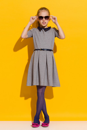 legs crossed at knee: Girl in sunglasses and gray dress posing in the sunlight. Full length studio shot on yellow background