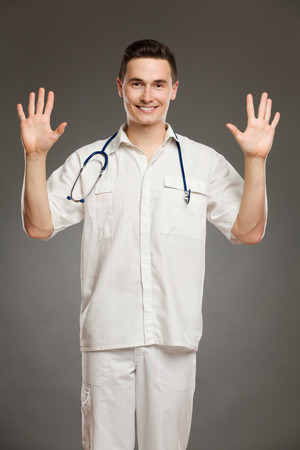three quarter length: Portrait of a smiling doctor showing number ten with his fingers. Three quarter length studio shot on gray background.