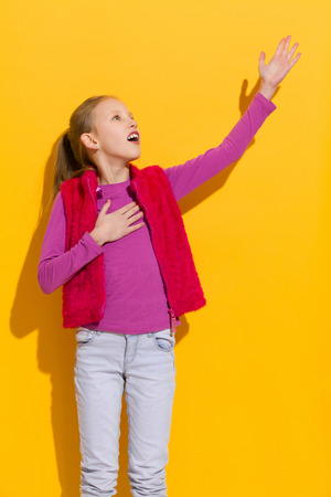 teen girls: Young blond singing with arm raised. Three quarter length studio shot on yellow background.