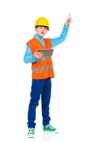 reflective vest: Young boy in yellow hard hat and orange reflective vest holding a digital tablet and pointing up. Full length studio shot isolated on white.