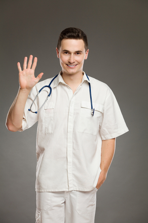 fingers: Portrait of a smiling doctor showing number five with his fingers. Three quarter length studio shot on gray background. Stock Photo