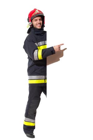 casco rojo: Bombero en casco rojo de pie detrás de gran pancarta y apuntando. Estudio de longitud completa aislado disparo en blanco. Foto de archivo