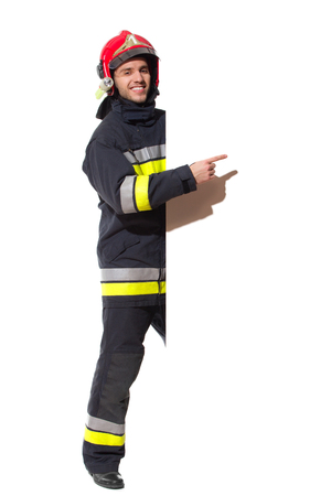 Firefighter in red helmet standing behind big placard and pointing. Full length studio shot isolated on white. Фото со стока