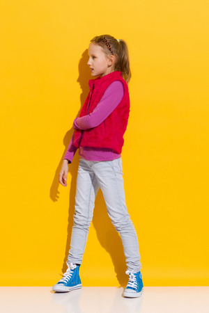 pink fur: Young blond girl posing in pink fur vest. Full length studio shot on yellow background.