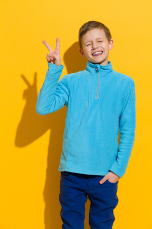 preadolescence: Funny boy posing with eyes closed and showing victory or peace sign. Three quarter length studio shot on yellow background.